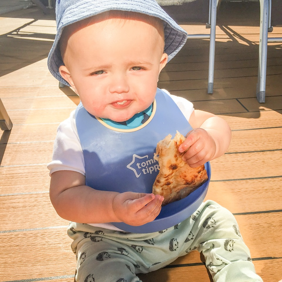 baby with pizza on deck
