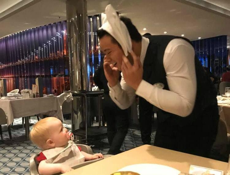 Royal Caribbean waiter entertaining baby